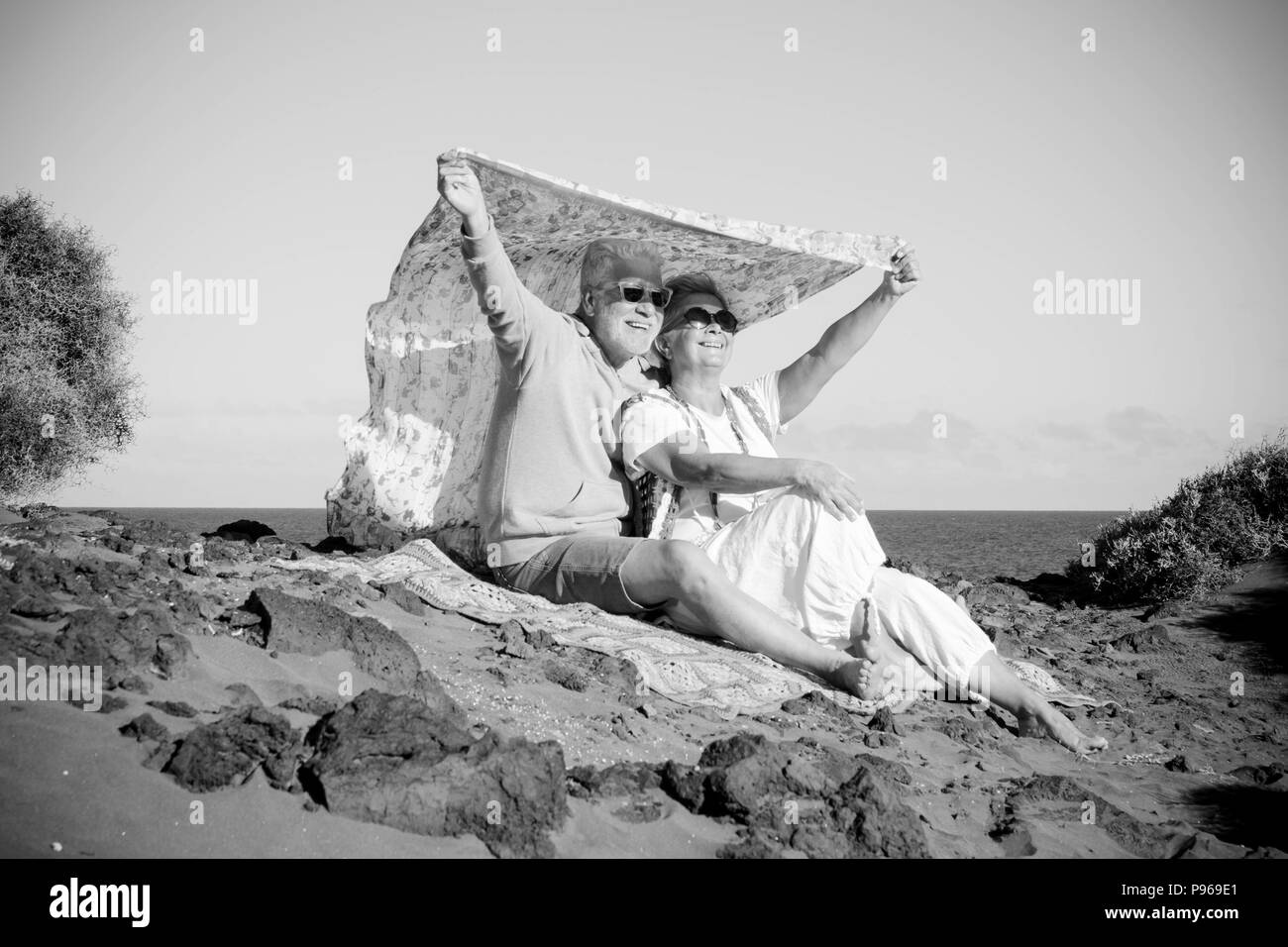 couple of senior caucasian hippy style and life rest on the rocky beach in tenerife. colors and alternative lifestyle for totally freedom concept near Stock Photo