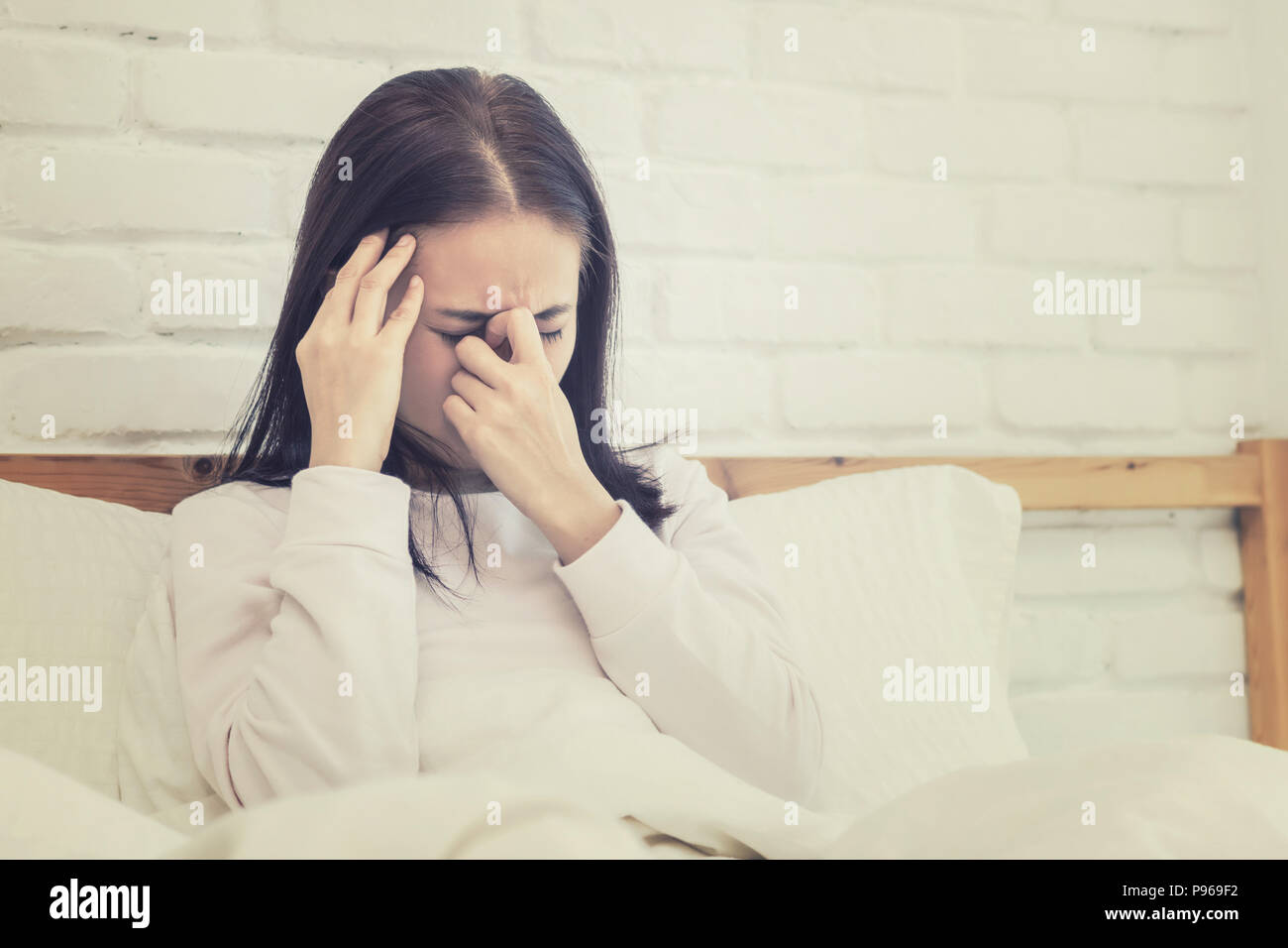 Asian woman sitting and sad on bed with hand touching his head sitting on bed - Stock Image