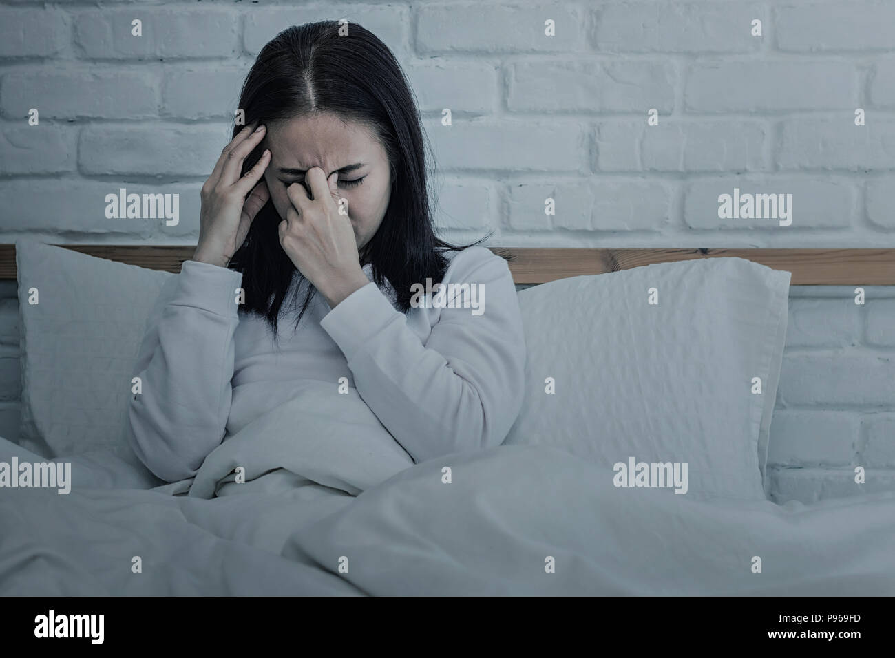 Asian woman sitting and sad on bed with hand touching his head sitting on bed.color tone - Stock Image
