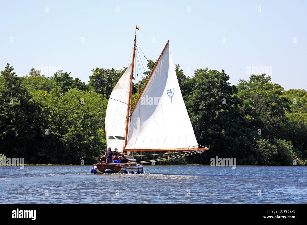 A yacht in full sail on a fair breeze on the River Bure on the Norfolk Broads near Horning, Norfolk, England, United Kingdom, Europe. - Stock Image