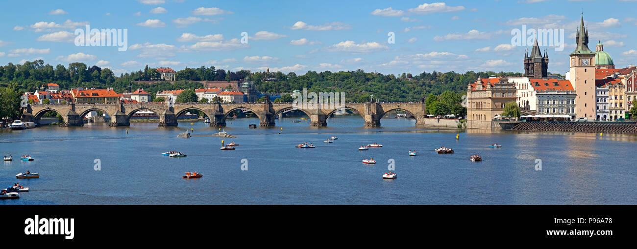 Charles Bridge with tourists, Vlelva river with pleasure boats, pedalo - Stock Image