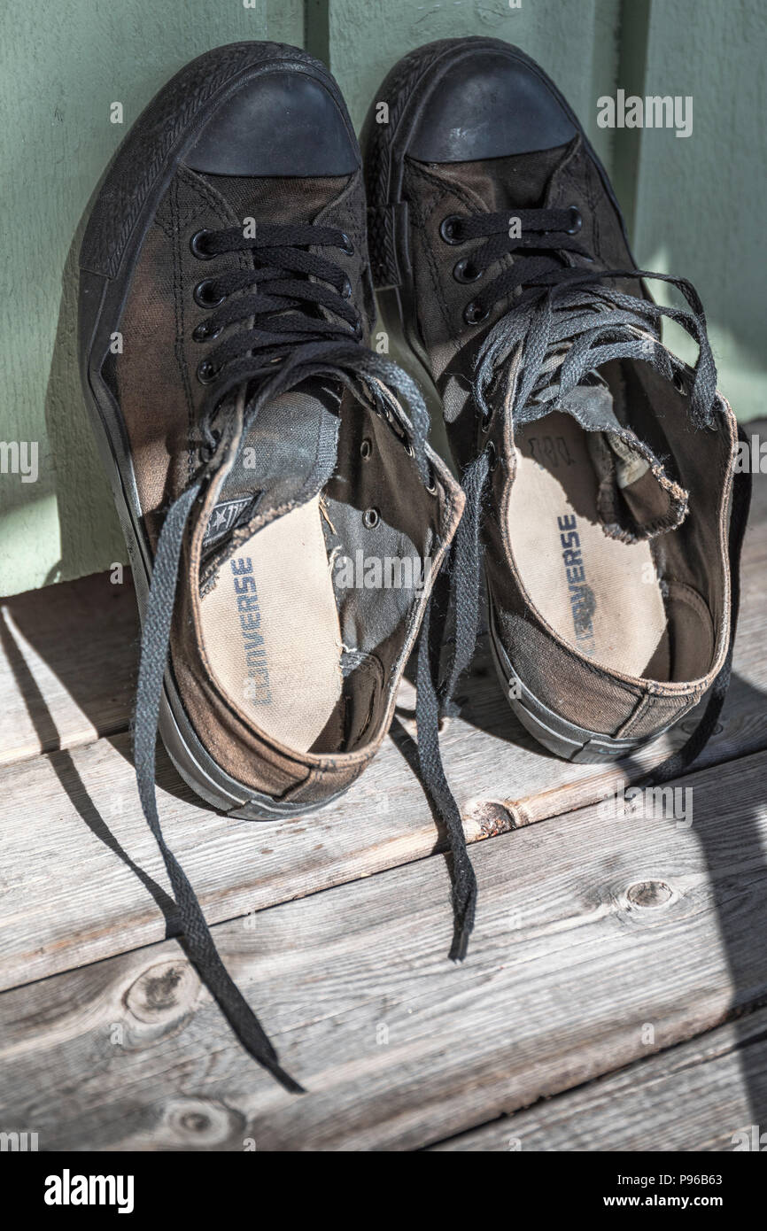 Close up view of black classic worn out Converse All Star shoes leaning up against wall - Stock Image