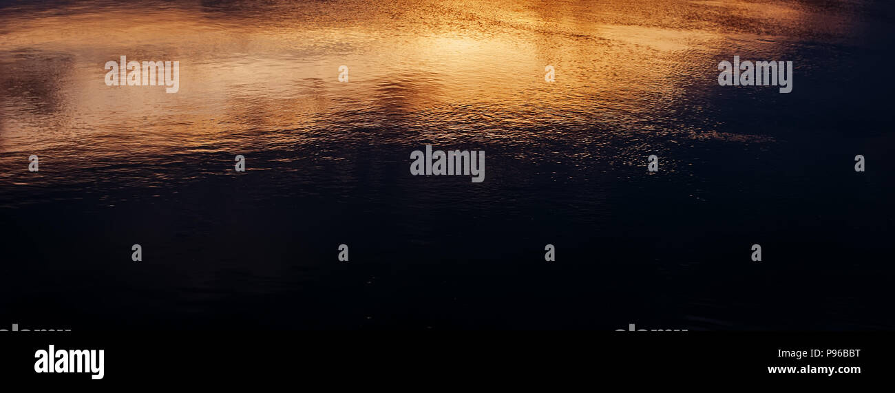 Reflection of the evening sky on the surface of the water in the river, panorama. Blurred background. Web Banner. - Stock Image