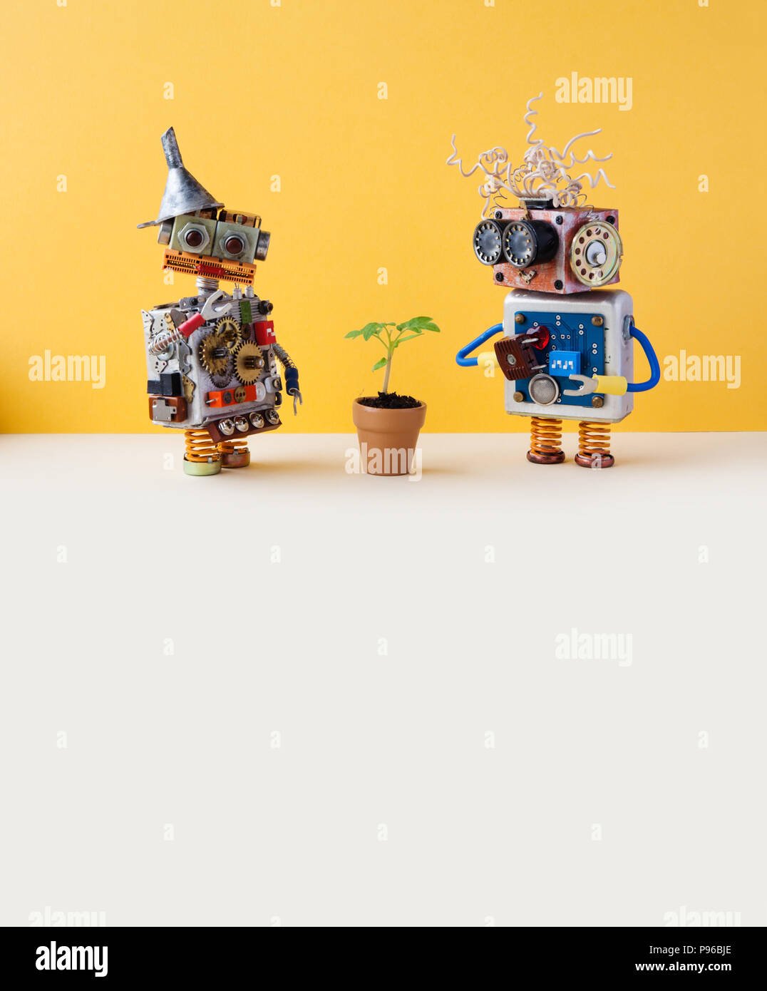 Two friendly robots and green plant in a flower clay pot. Technology versus organic life plant concept. Yellow wall background, white floor. Copy space. - Stock Image