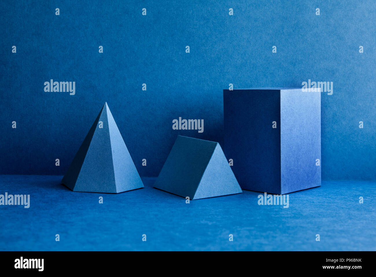 Geometrical figures still life composition. Three-dimensional prism pyramid tetrahedron rectangular cube objects on blue background. Platonic solids figures, simplicity concept photography. - Stock Image