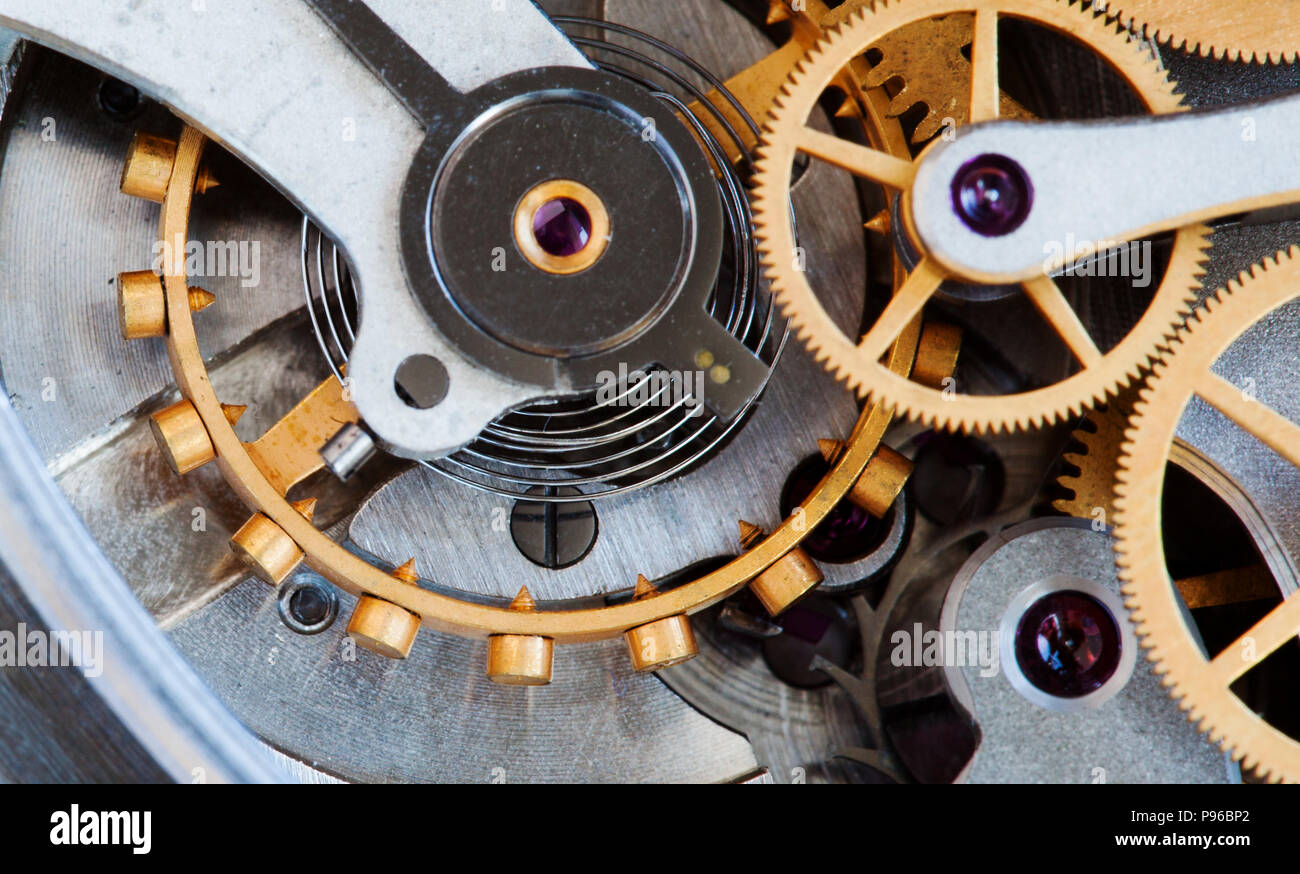 Clock transmission macro view. Stopwatch chronometer mechanism cogs gears wheels connection concept. Shallow depth of field, selective focus - Stock Image