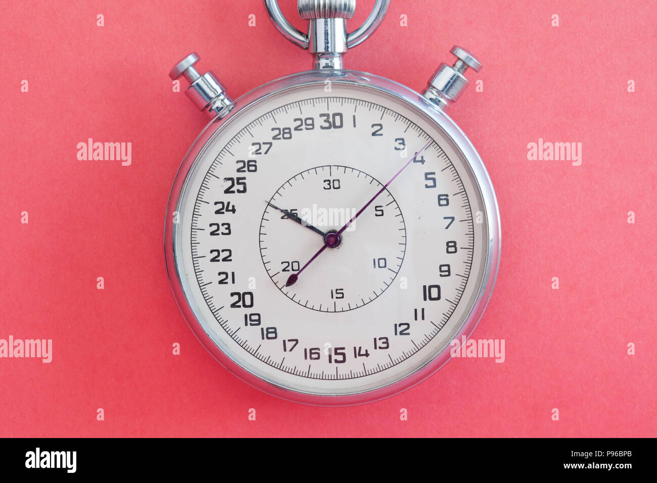 Retro style stopwatch chronometer on pink paper textured background. Sport competition time management concept. Macro view, soft focus - Stock Image