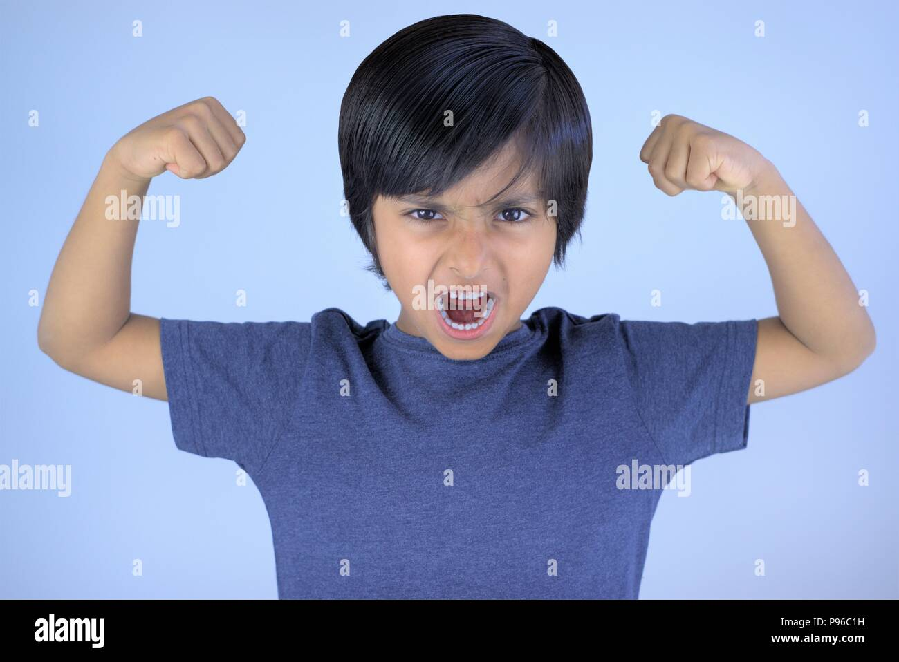 Angry kid screaming or yelling with raised arms and closed fists - Stock Image