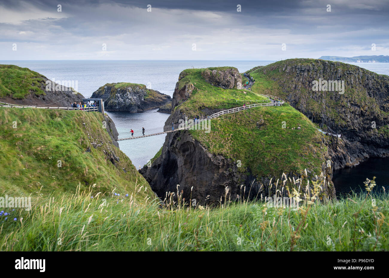 Tourists walking on the Carrick-a-Rede rope bridge on the Causeway Coast in County Antrim, Northern Ireland - Stock Image