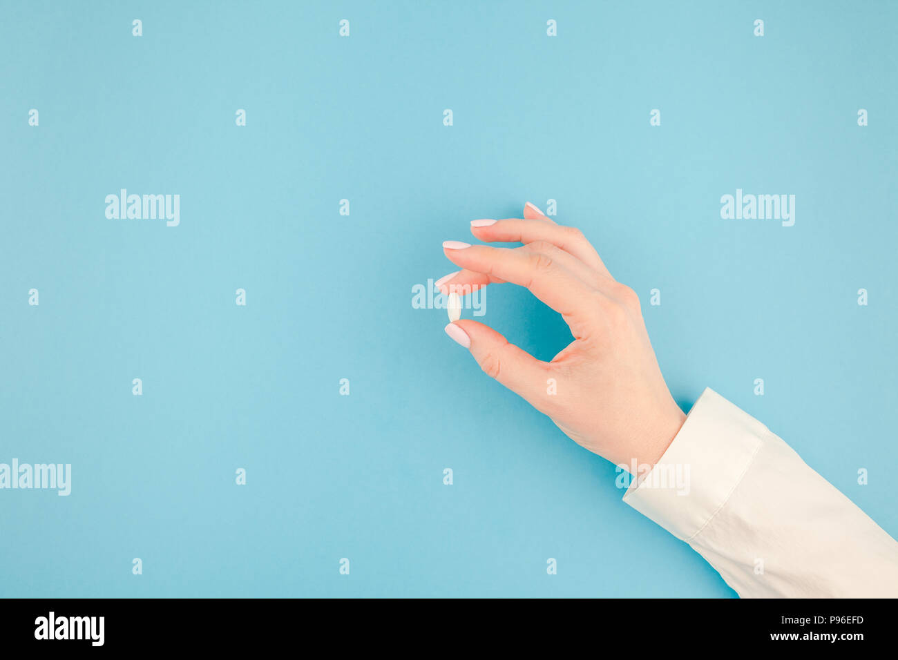 woman hand holding a white pill on pastel blue paper background with