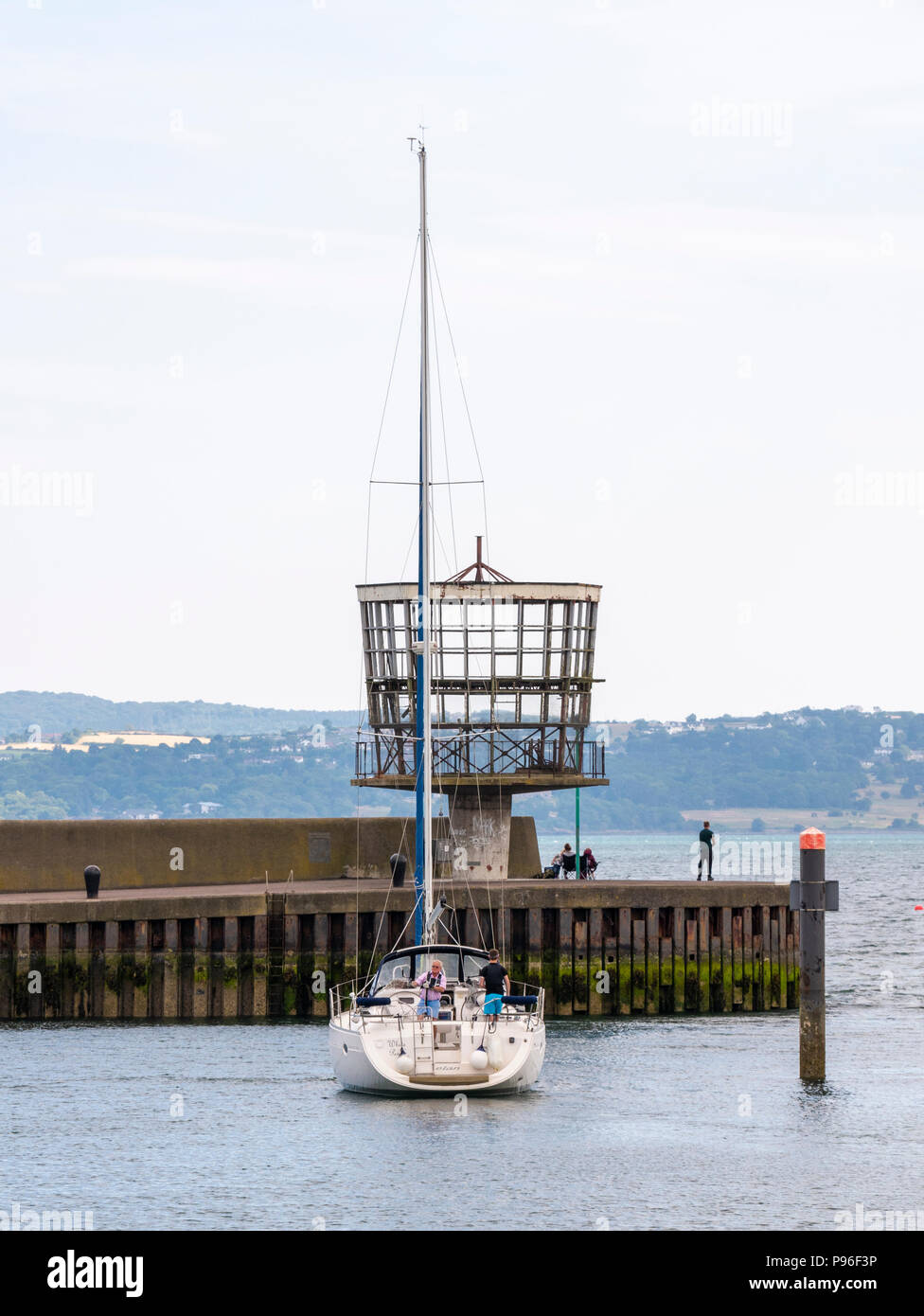 A yacht sails past the derelict Radio Control Tower, Carrickfergus, Northern Ireland. The tower was originally used to monitor shipping in Belfast Lou - Stock Image