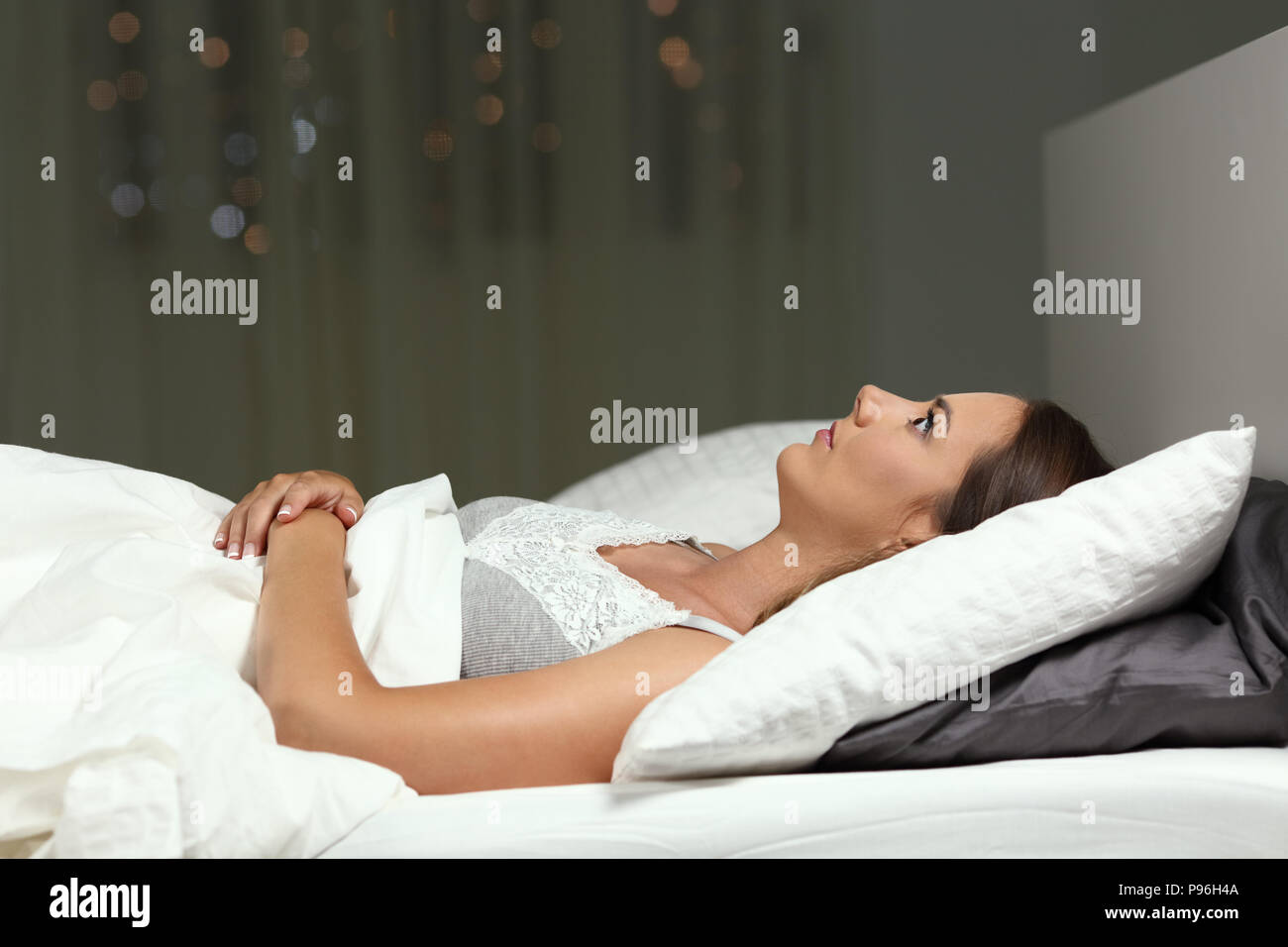 Side view portrait of a insomniac girl unable to sleep in the night on a bed - Stock Image