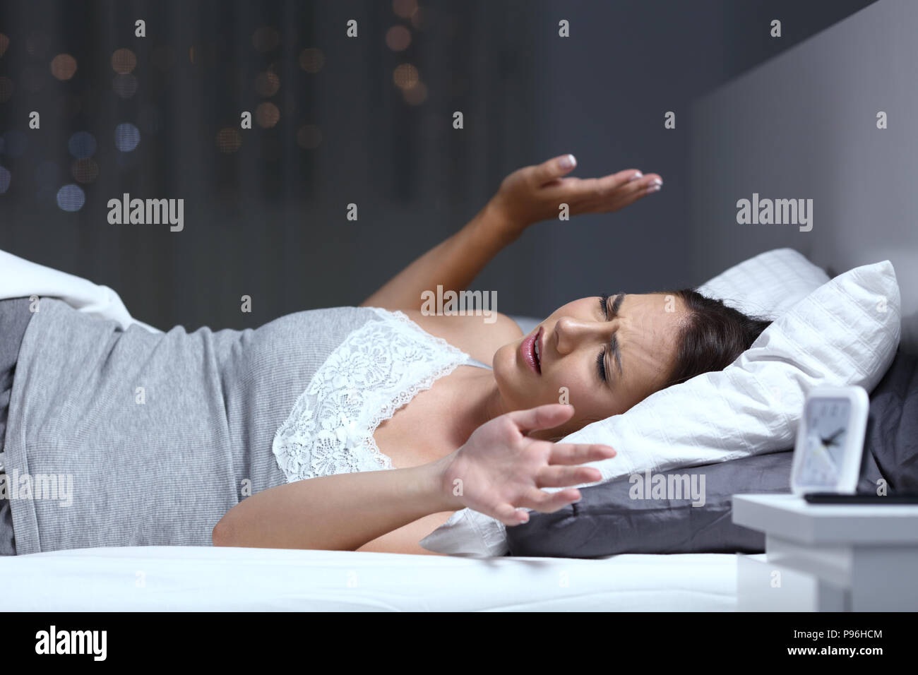 Woman having a nightmare lying on the bed in the night at home - Stock Image
