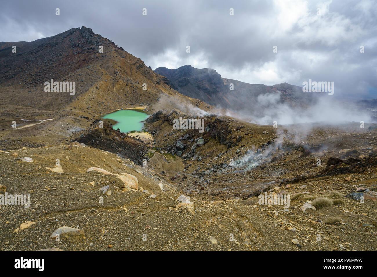 hiking the tongariro alpine crossing,lake and smoke in volcanic crater,new zealand - Stock Image