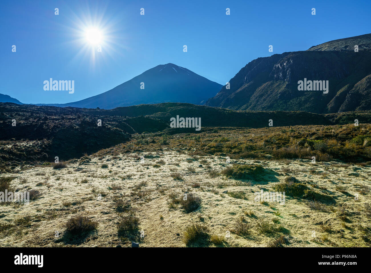hiking the tongariro alpine crossing,sunstar over cone volcano mount ngauruhoe,new zealand - Stock Image