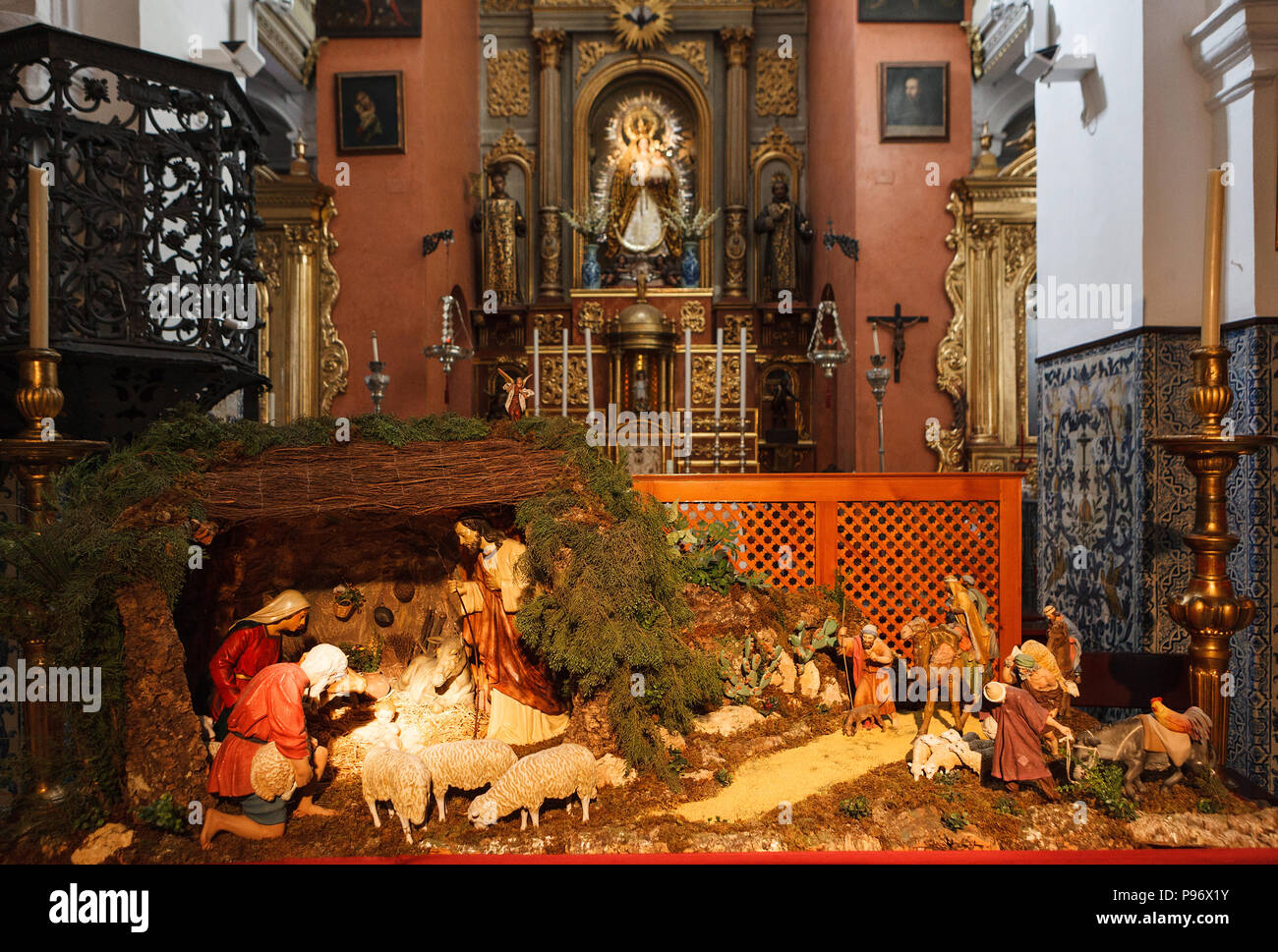 christmas manger scene with figurines including jesus mary joseph sheep and magi facing the altar in the christianity church iglesia de san ildefo