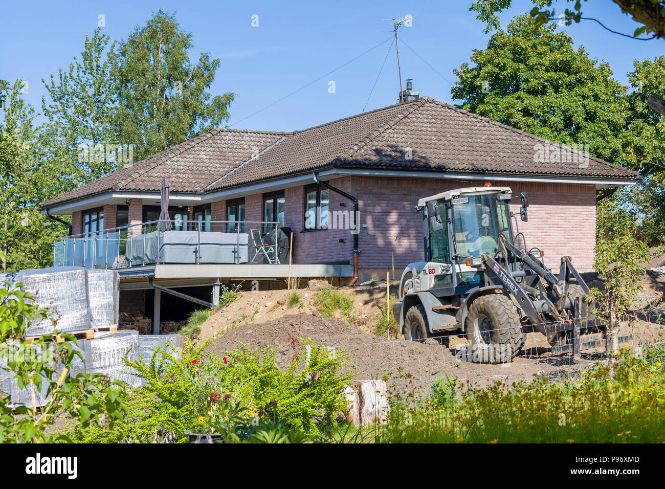 FLODA, SWEDEN - JULY 15 2018: Detached house undergoing home improvement and landscaping with front garden filled with building supplies such as brick - Stock Image