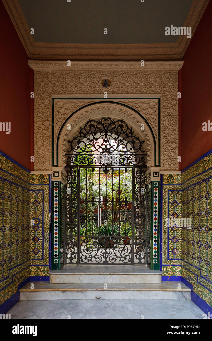 Doorway to courtyard (patio) in Seville, Andalusia, Spain. Decorated with mixing elements of the Renaissance Revival and Moorish Revival (Neo-Mudejar) - Stock Image