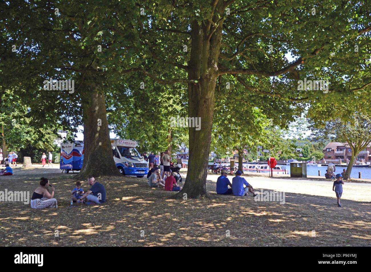 People sitting under a tree on a hot day beside the River Thames in Marlow, Buckinghamshire, England, UK - Stock Image