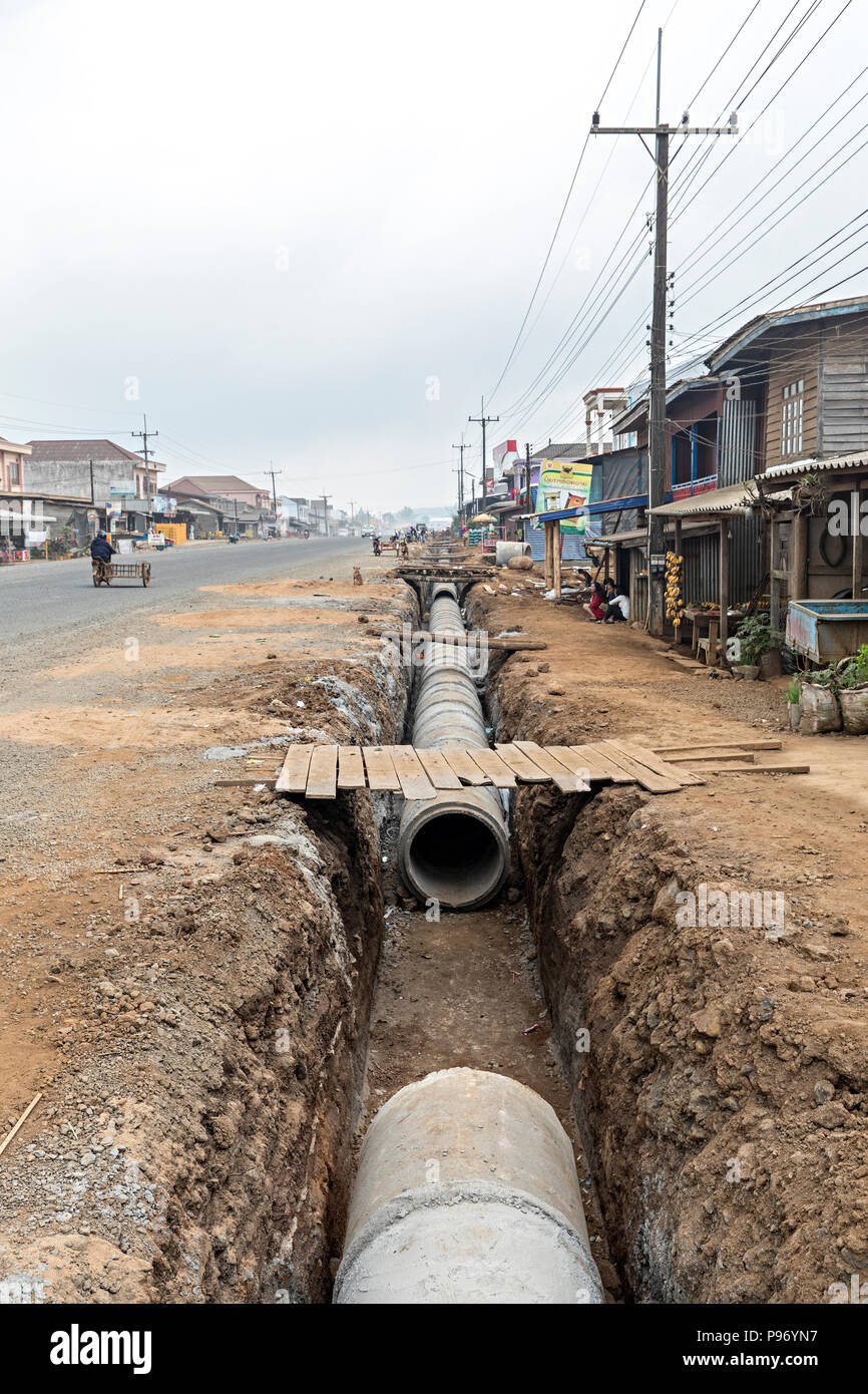 Laying new pipe in trench through town, Paksong, Laos - Stock Image