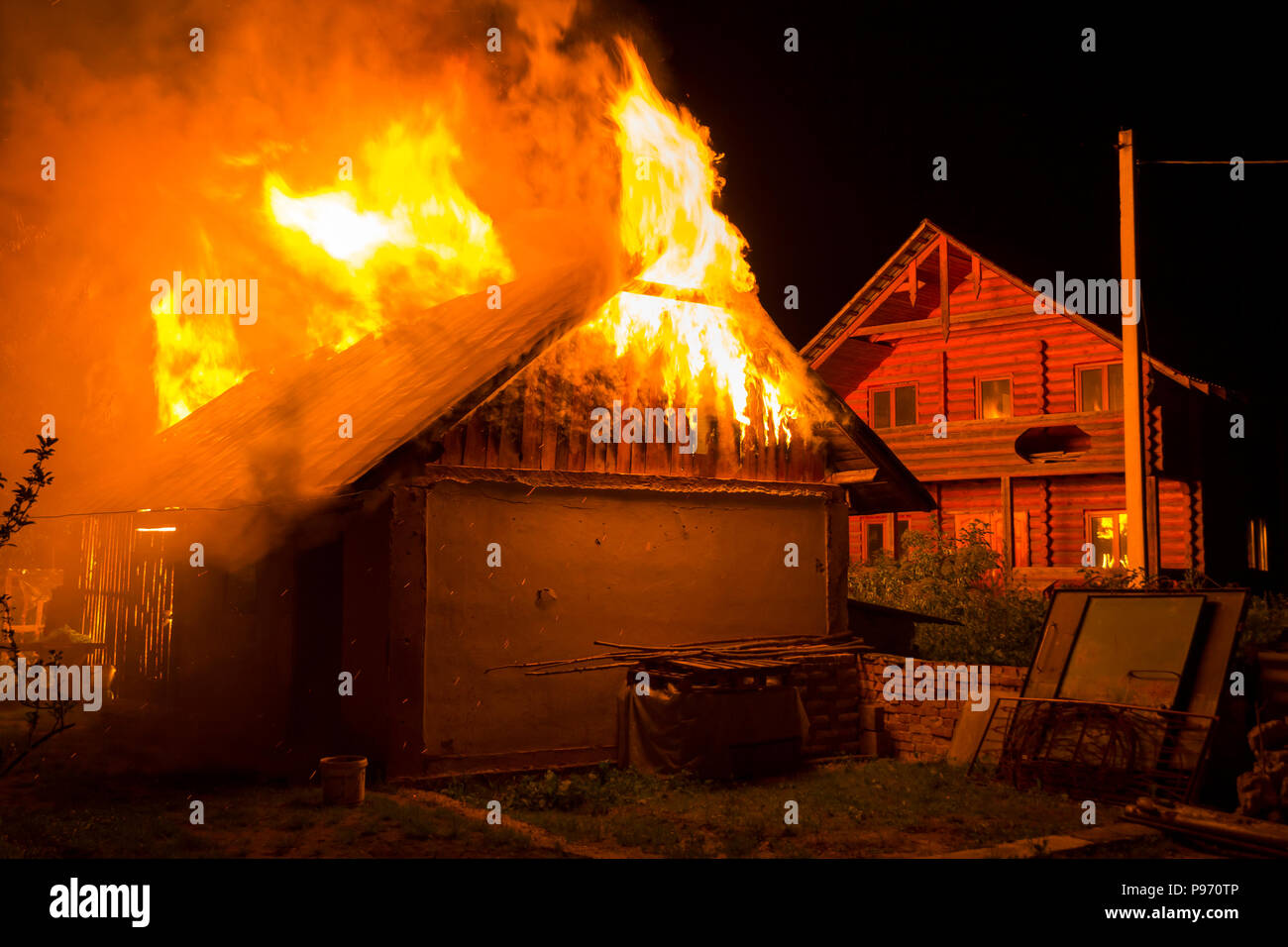 wooden barn burning at night high orange fire flames dense smoke