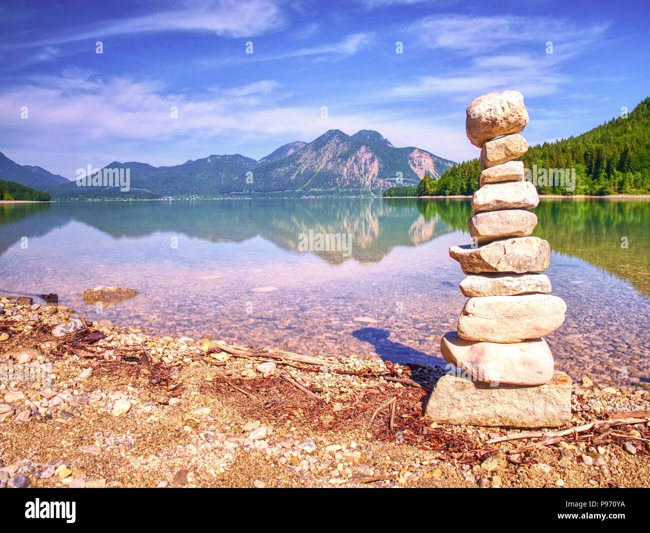 Building of stone pyramide on shore of blue water of mountain lake. Blue mountains in water level mirror - Stock Image