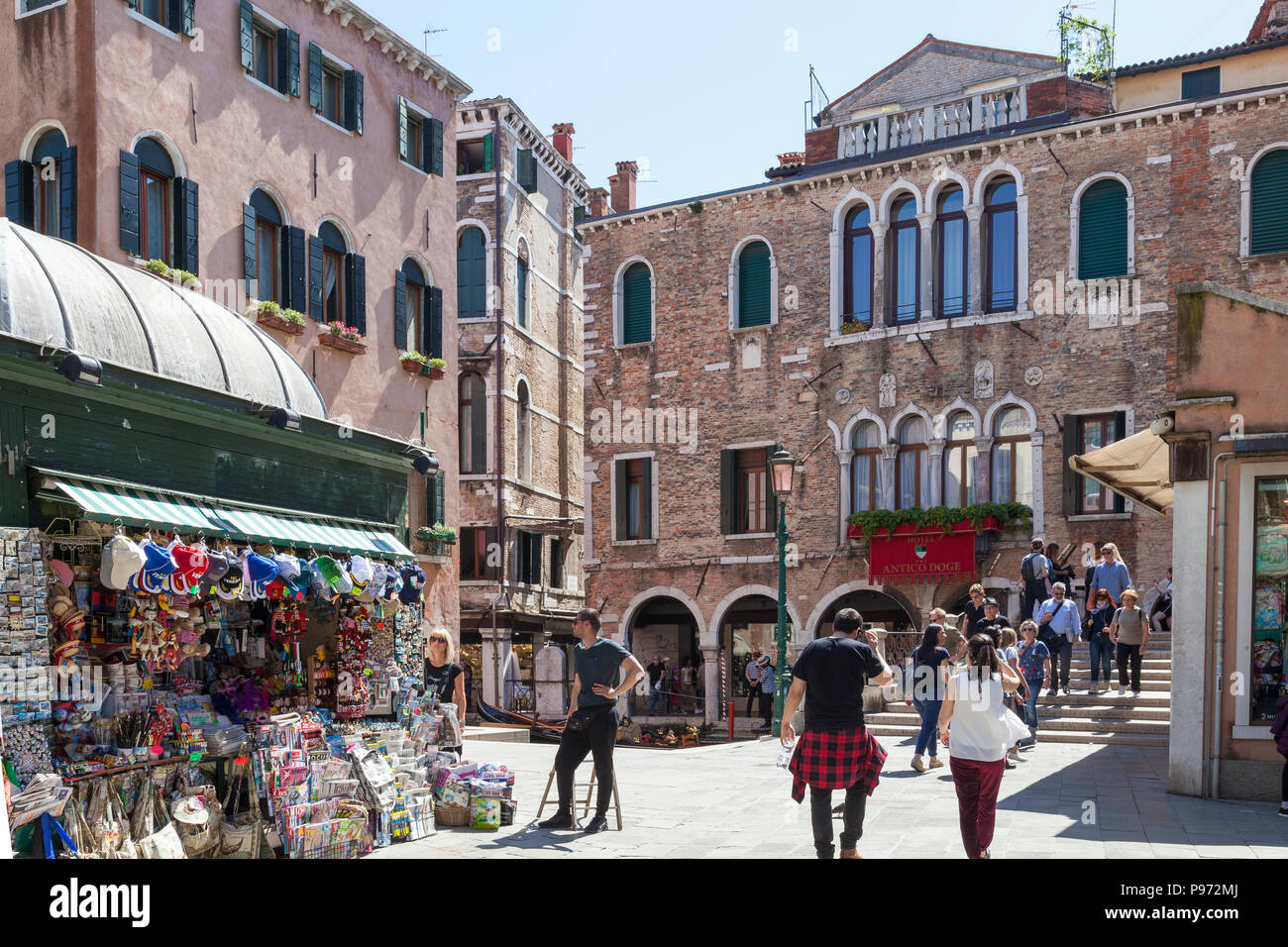 Campo Santi Apostoli and the Antico Doge Hotel, Cannaregio, Venice, Veneto, Italy with a news agent selling souvenirs and tourists - Stock Image