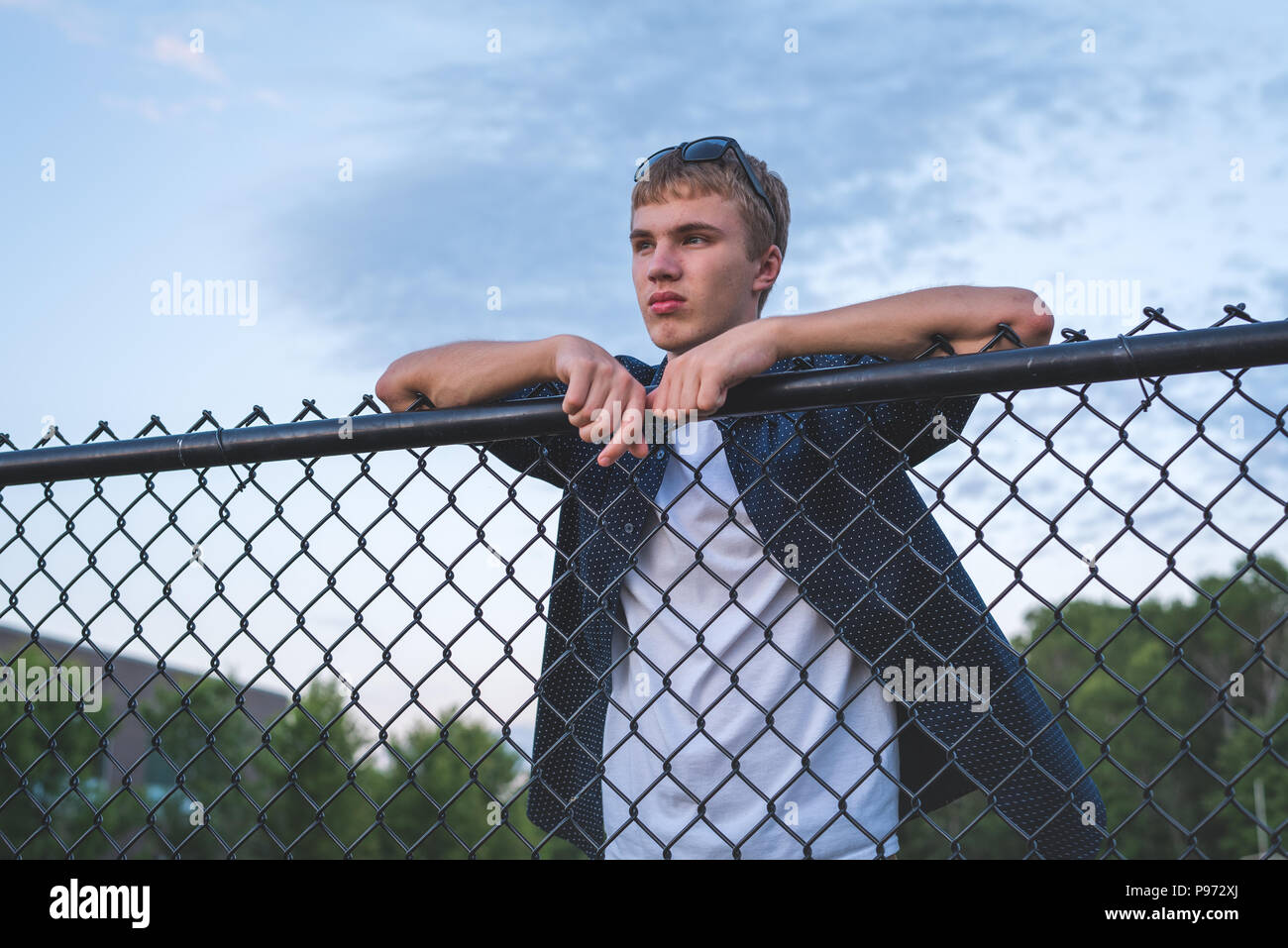 Sad teenager leaning against a chain link fence. - Stock Image