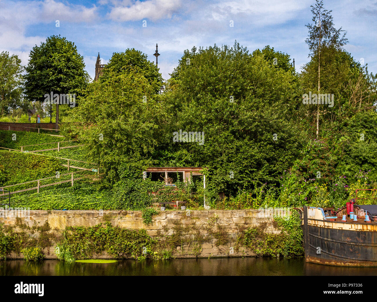 Stroll along the canal in Leeds one sunny afternoon. A ruin shed taken over by Nature and a rusty boat moored to the bank. - Stock Image