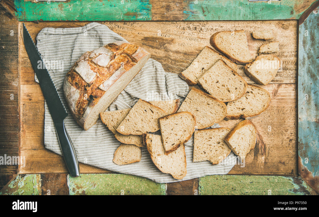 Flat-lay of sourdough wheat bread cut in slices in tray - Stock Image