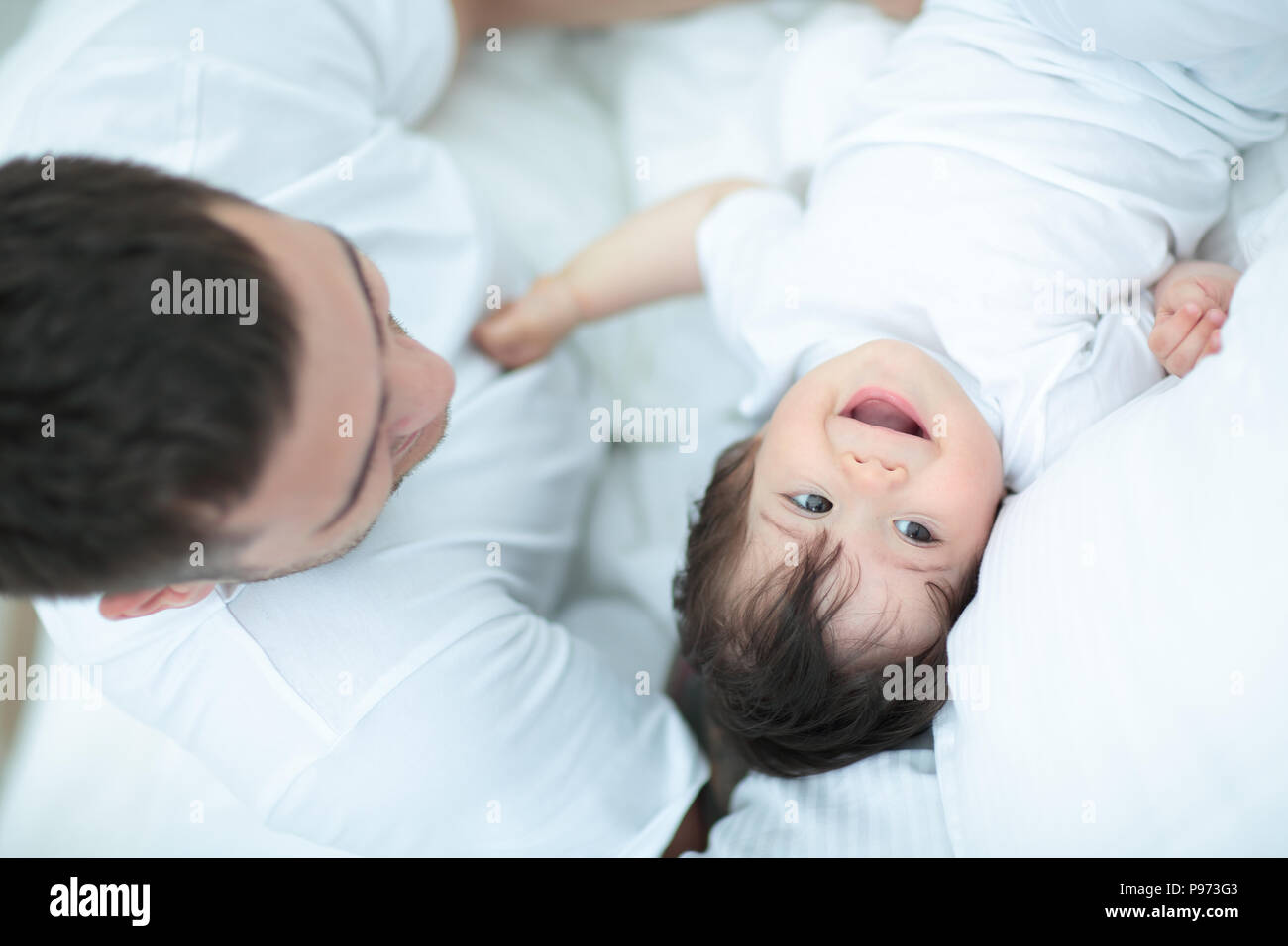 Smiling father with his  baby son hugging in bed - Stock Image