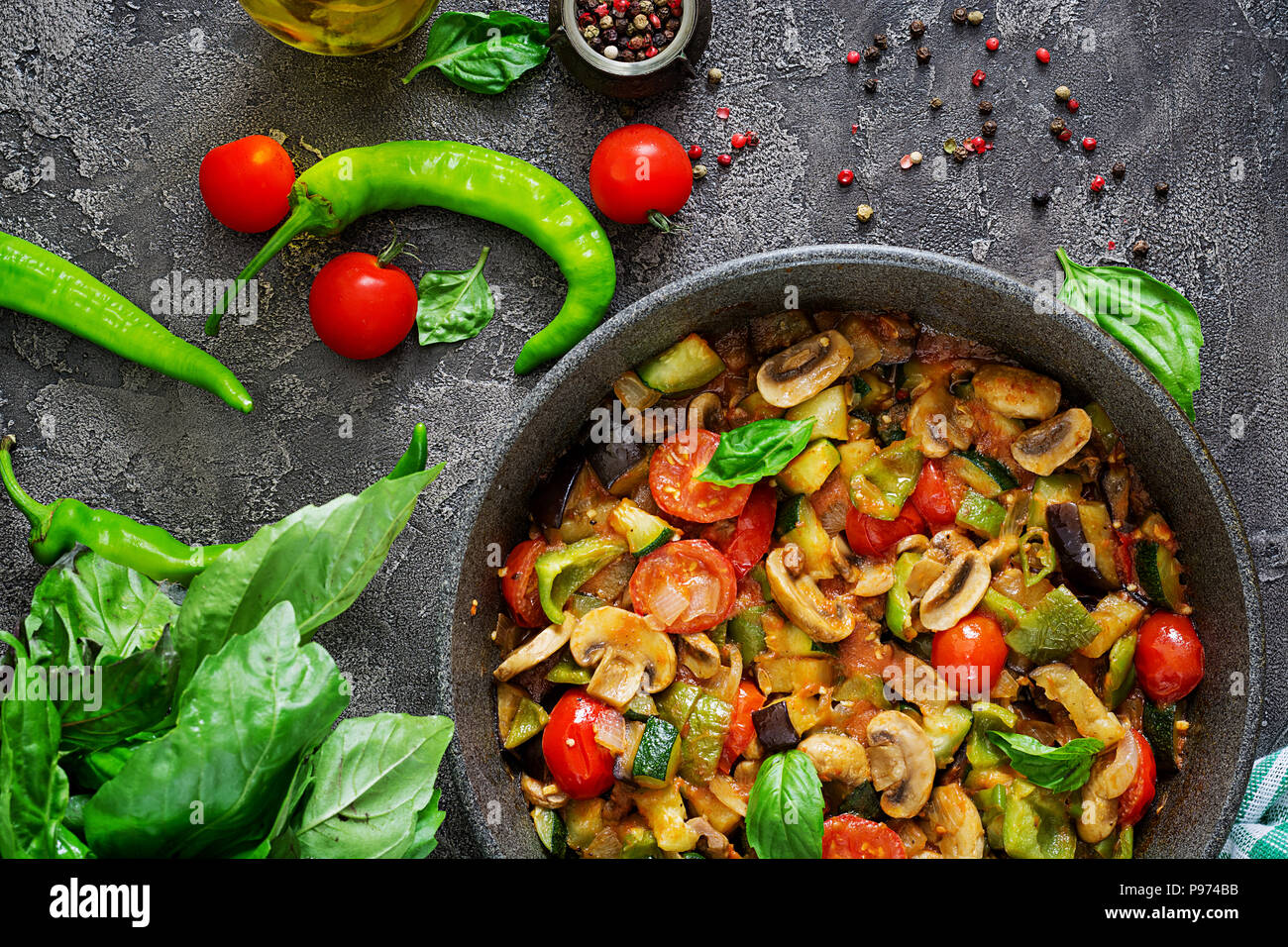 Hot spicy stew eggplant, sweet pepper, tomato, zucchini and mushrooms. Flat lay. Top view - Stock Image