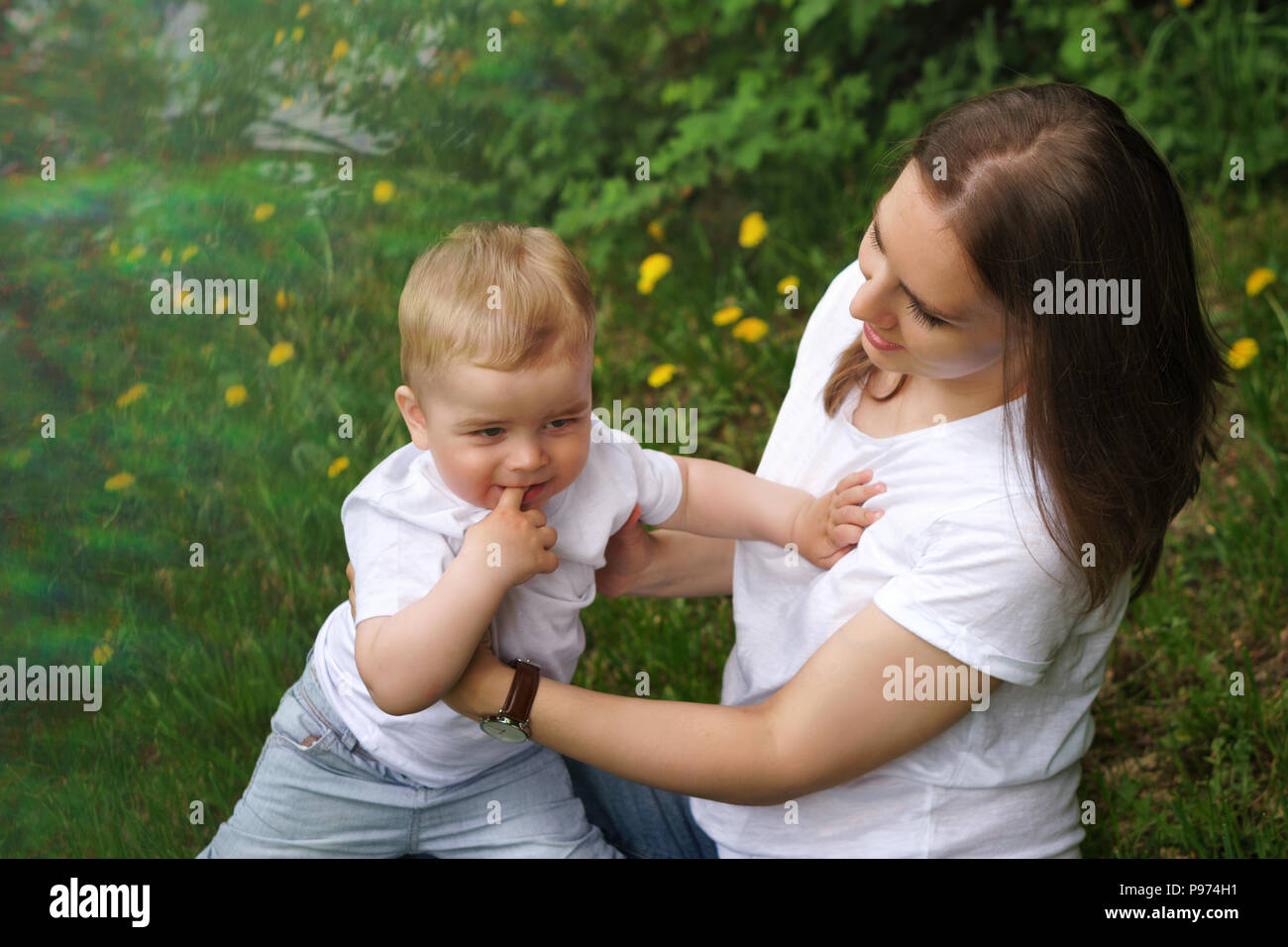 Young pregnant girl sits on lawn in city park. Mother supports her son. Little boy bites his finger. Happy motherhood. Blur effect Stock Photo