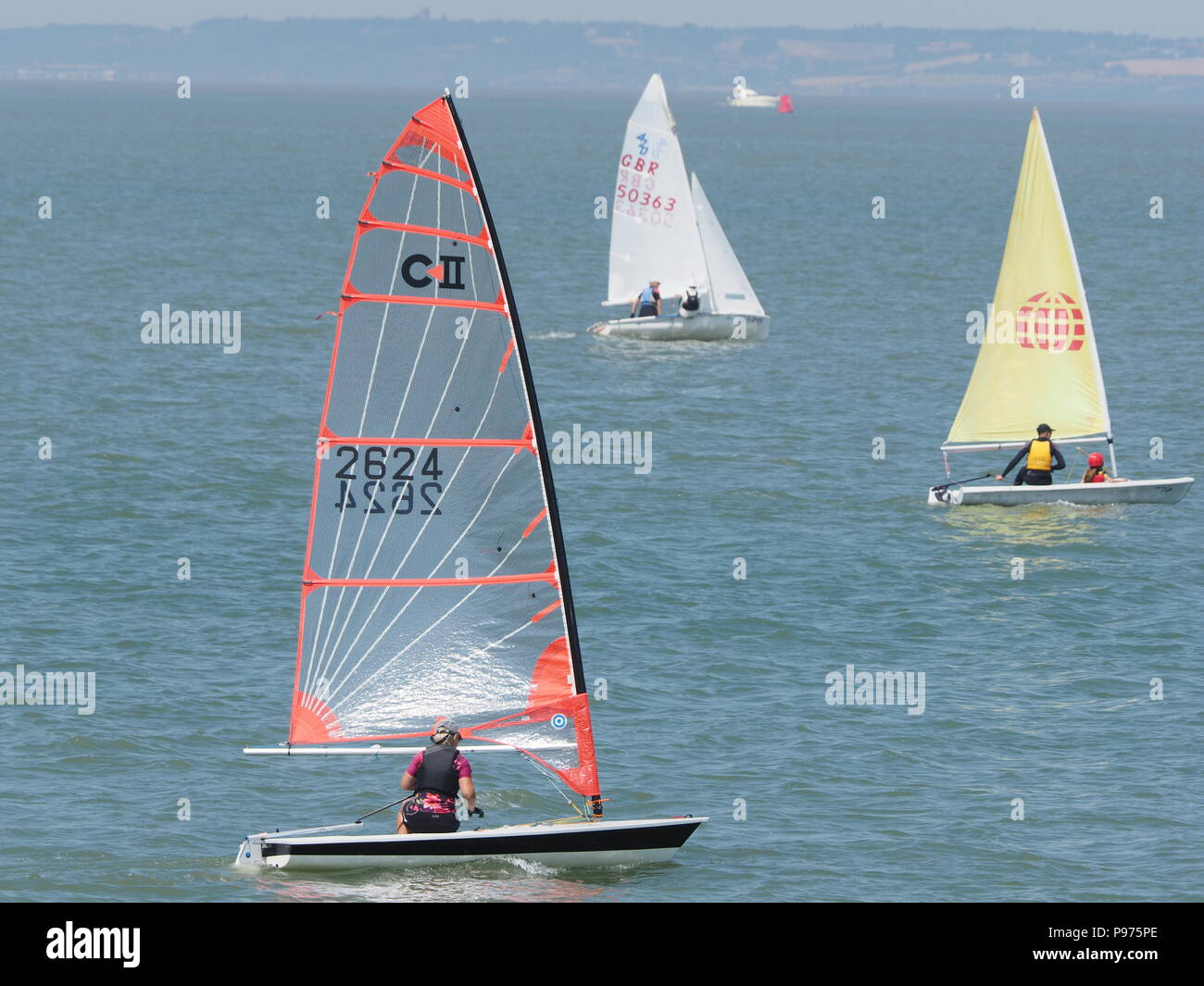 Sheerness, Kent, UK. 15th July, 2018. UK Weather: a sunny, dry and warm day at midday on St. Swithin's Day as members of the Isle of Sheppey Sailing Club take to the waters of the Thames Estuary off Sheerness in Kent. Credit: James Bell/Alamy Live News - Stock Image