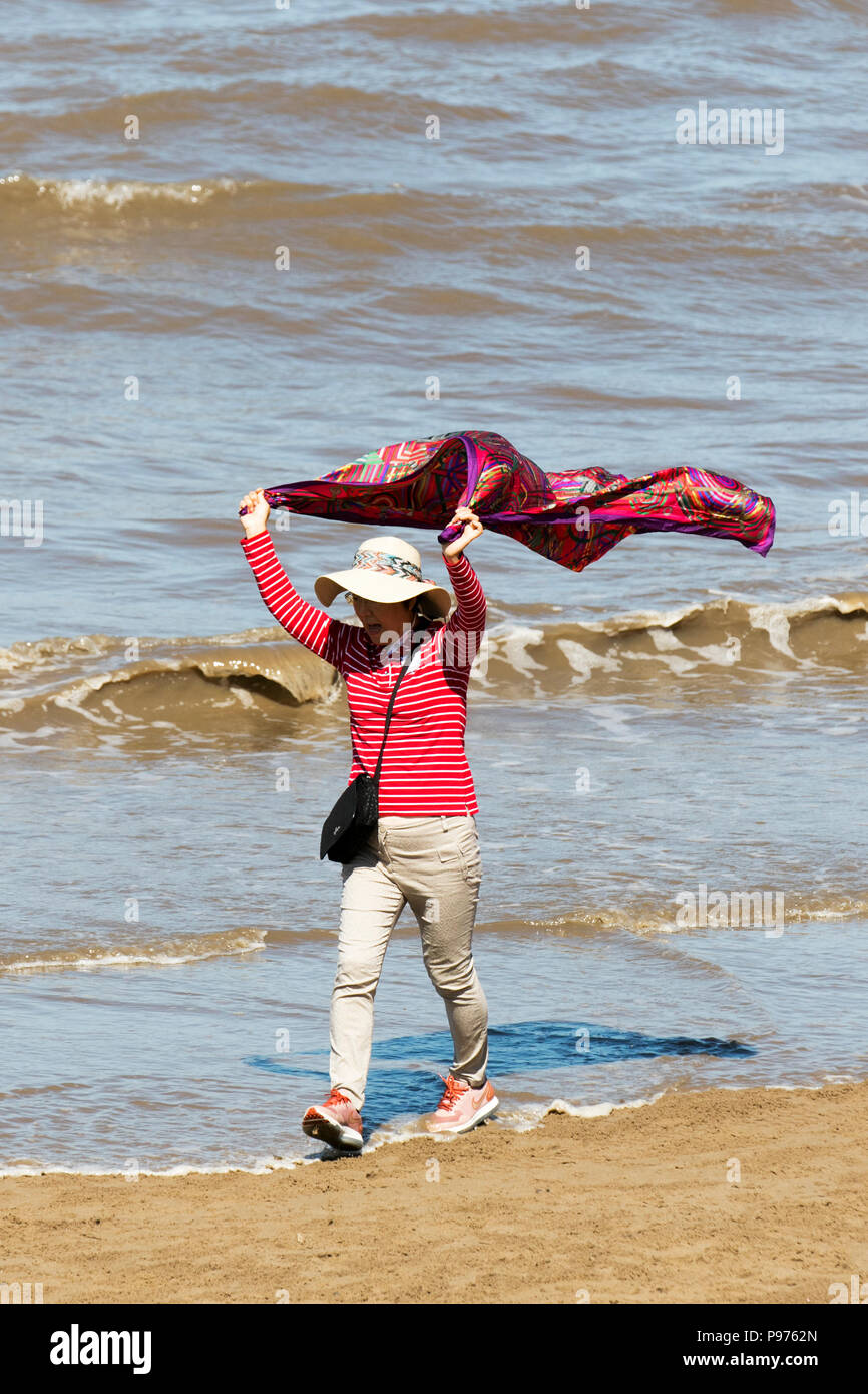 Blackpool, Lancashire, UK Weather. 15/07/2018. Fun & games as Chinese tourists from Yuanpei College, an elite liberal undergraduate college of Peking visit the Fylde coast for last sunny day for a while.  Cloud is forecast to build later with rain to follow and cooler temperatures. Many of the tourists rush to the beach only to be chased by the incoming high tide.  Credit: MediaWorldImages/AlamyLiveNews. - Stock Image