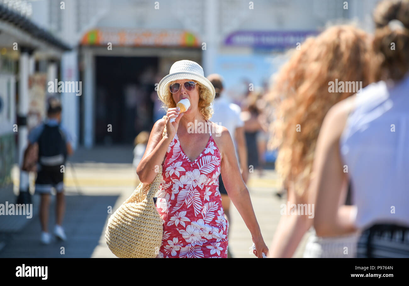 Brighton UK 15th July 2018 - Time to enjoy an ice cream on Brighton Palace Pier in glorious hot sunshine as the temperatures soar into the low 30s in some parts of the South East of Britain today Credit: Simon Dack/Alamy Live News - Stock Image