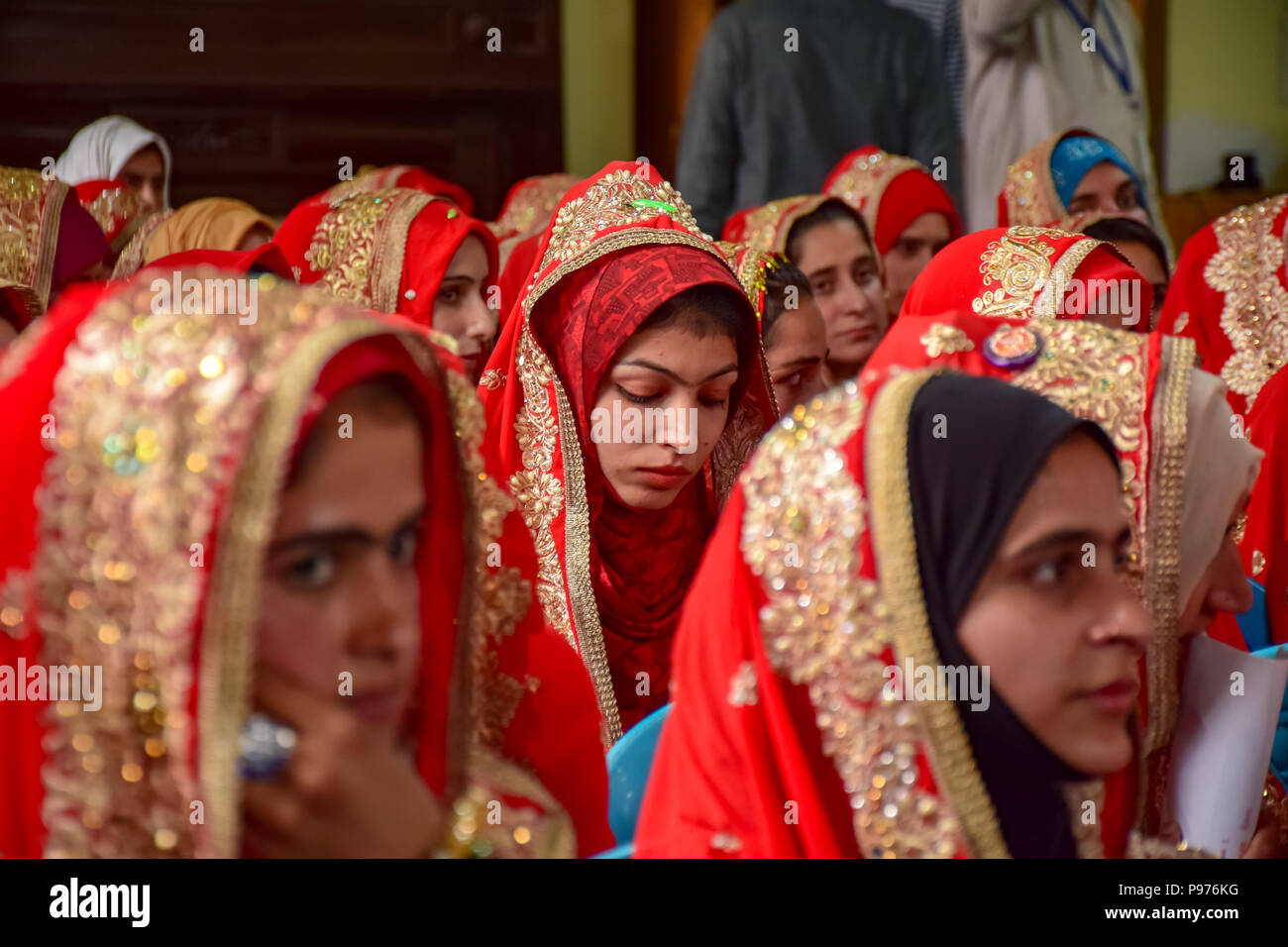 Srinagar, India. 15th July 2018. Kashmiri Muslim brides sit for a mass marriage event in Srinagar, Indian controlled Kashmir on Sunday. Mass wedding of 105 Muslim couples held in Srinagar organised by social welfare organisation primarily to help the economically backward families who cannot afford the high costs of the ceremony, dowry and expensive gifts, that still prevails in many communities of India. Credit: SOPA Images Limited/Alamy Live News - Stock Image