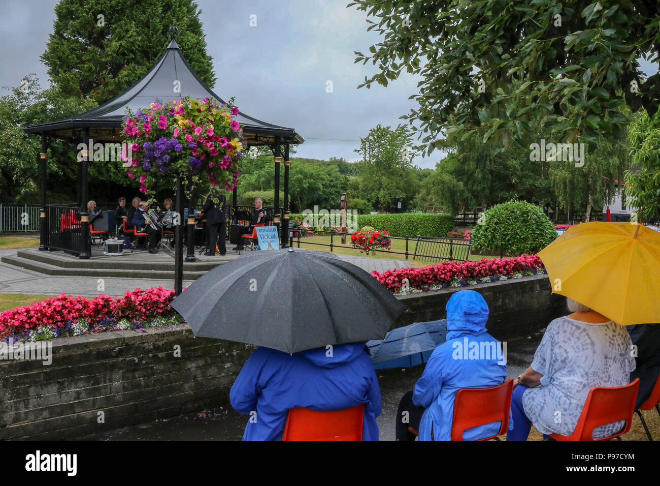 Scarva, County Down. 15 July 2018. UK weather - the prolonged spell of exceptionally dry weather came to an end today. Persistent rain was however welcome even if it meant a Sunday afternoon band concert under an umbrella. Credit: David Hunter Alamy Live News. - Stock Image