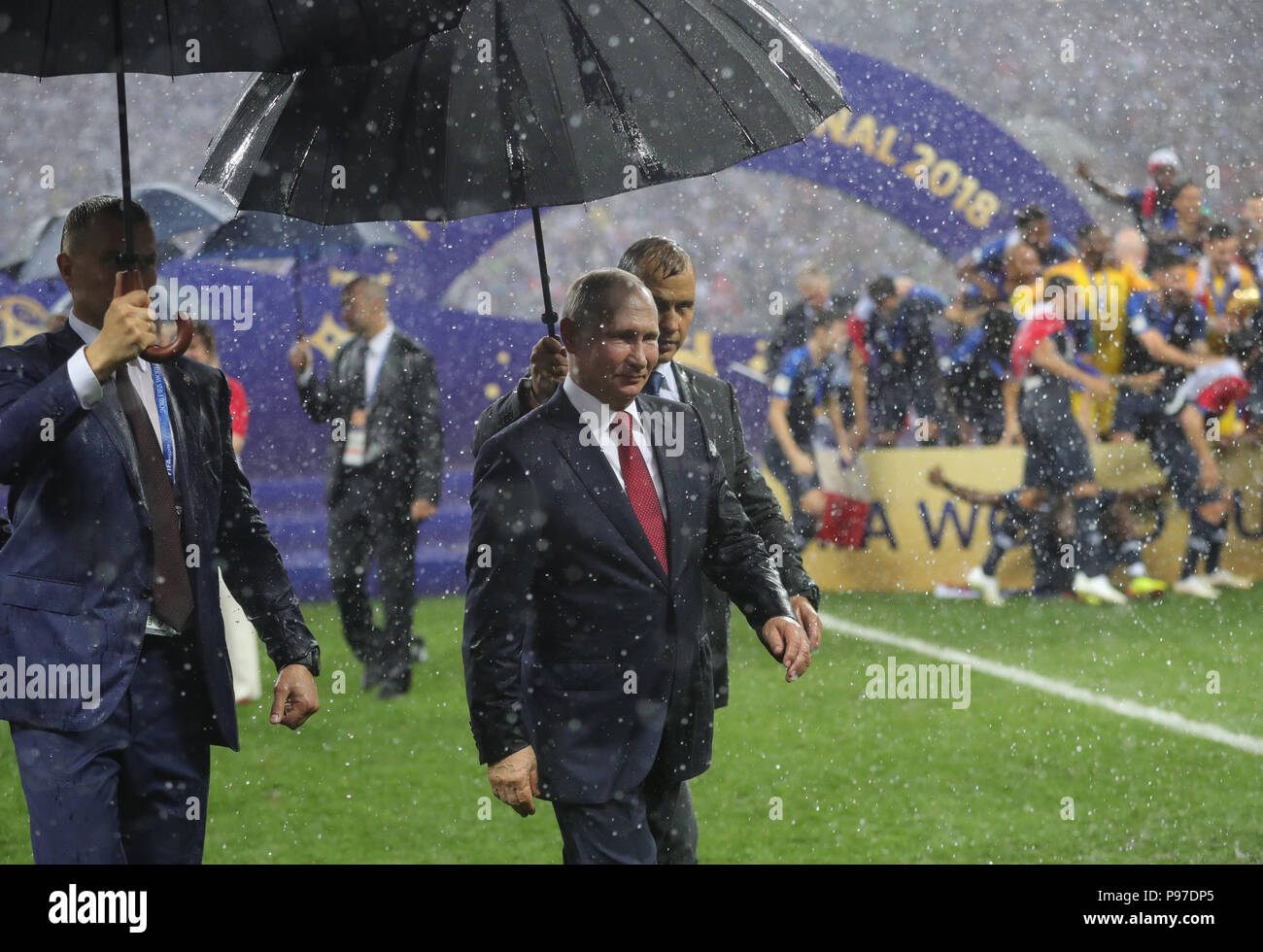 Moscow, Russia. 15th July, 2018. Soccer, World Cup 2018: Final game, France vs. Croatia at the Luzhniki Stadium. Vladimir Putin (L), President of Russia, under an umbrella in the pouring rain after the France's victory. Credit: Christian Charisius/dpa/Alamy Live News - Stock Image