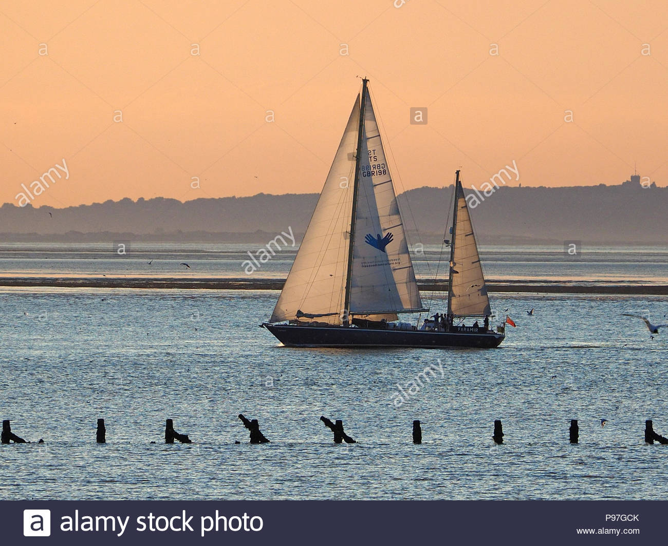 Sheerness, Kent, UK. 15th July, 2018. UK Weather: the yacht 'Faramir' as it arrives at Garrison Point, Sheerness at sunset. The 23m / 75ft yacht Faramir is a Bermudan ketch operated by the Cirdan Sailing Trust which provides challenge and adventure for young people. Credit: James Bell/Alamy Live News - Stock Image