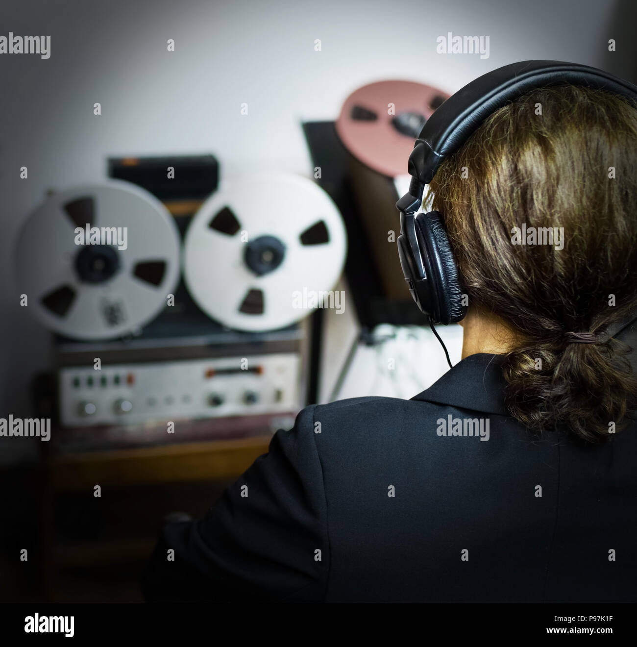 a woman listens at headphones to some secret recordings - Stock Image