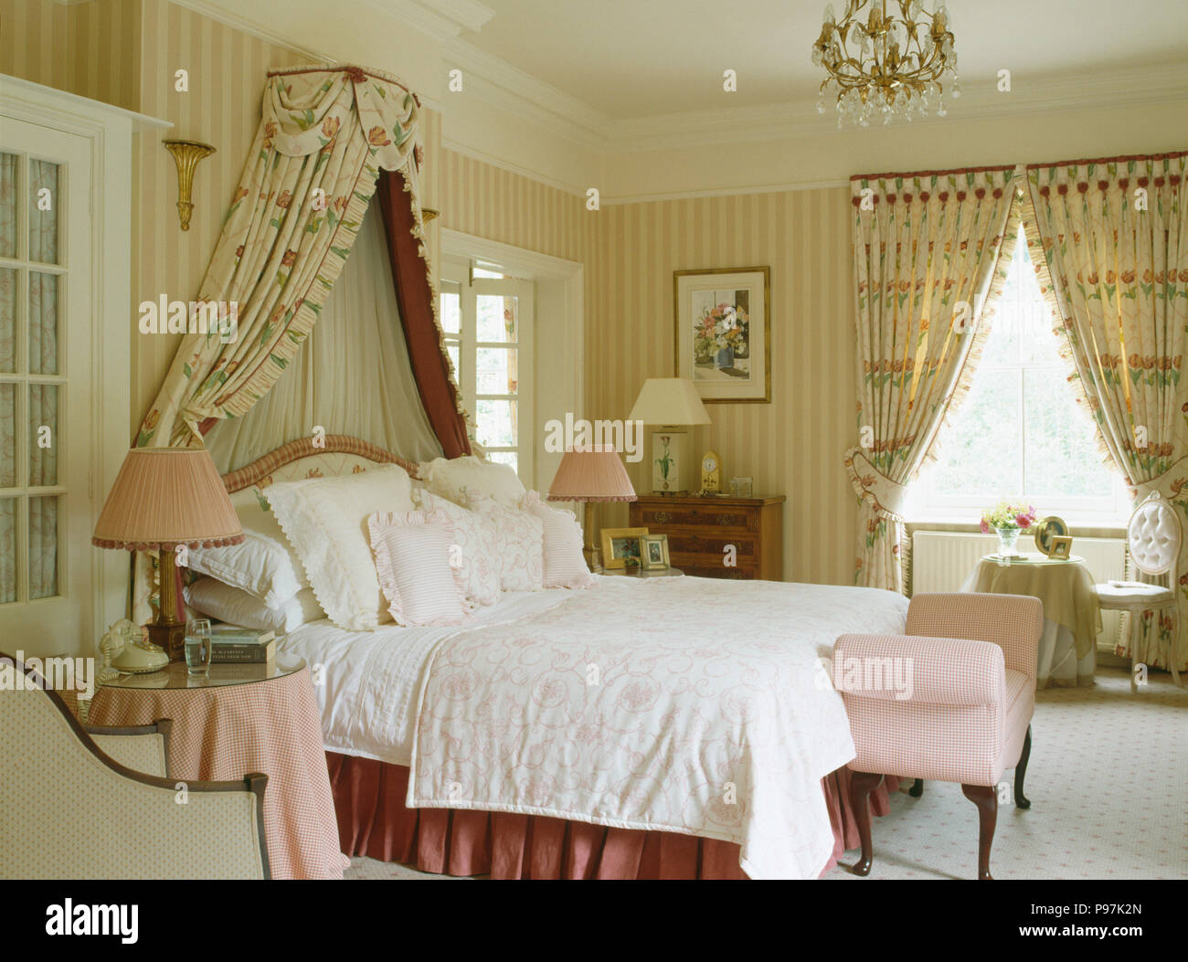 Coronet With Floral Drapes Above Bed Piled With Cushions In Country