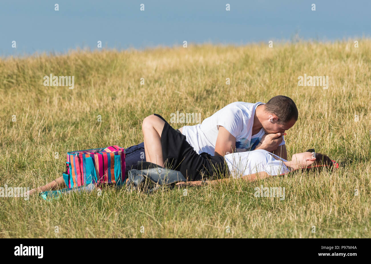 Young man and woman laying together in a field on a warm summer evening sharing an intimate moment. Young couple in UK. NOTE:They may not be a couple. - Stock Image