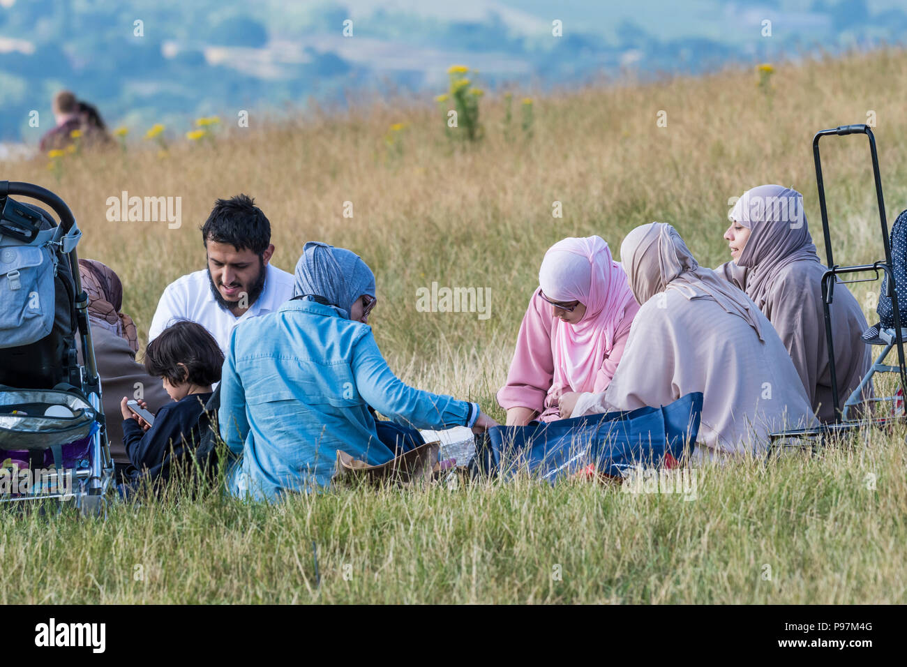 Asian family eating (having a picnic, picnicking) outside in the British countryside in East Sussex, England, UK. - Stock Image