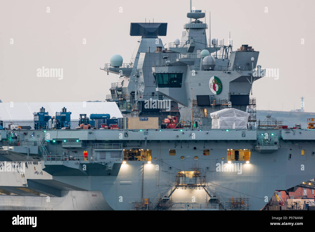 HMS Queen Elizabeth Aircraft Carrier, the Royal Navy's largest and newest warship, moored at dusk in the docks at Portsmouth, Hampshire, England, UK. - Stock Image