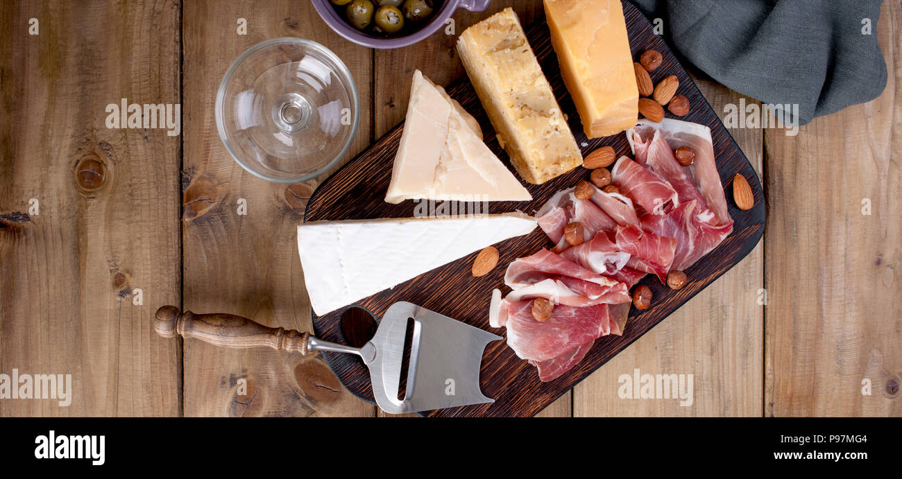 Assorted cheese, meat and olives. A delicious Italian snack for a party. Copy space . Banner - Stock Image