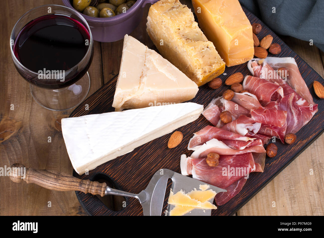 Assorted cheese, meat, wine in a glass and olives. A delicious Italian snack for a party. View from above. Copy space - Stock Image