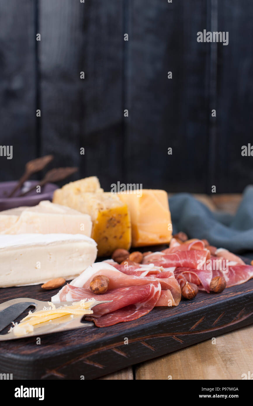 Assorted cheese, meat and olives. A delicious Italian snack for a party. Copy space - Stock Image