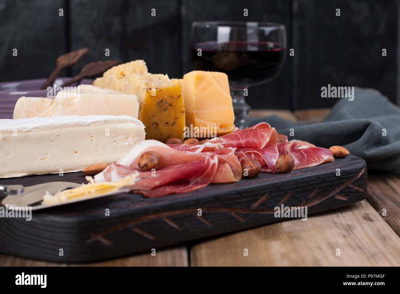 Assorted cheese, meat, wine in a glass and olives. A delicious Italian snack for a party. Copy space - Stock Image
