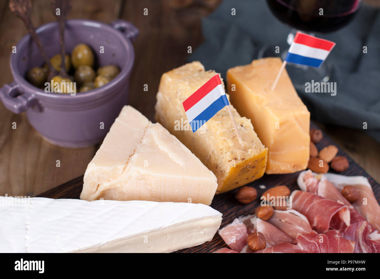 Assorted cheese, meat, wine in a glass and olives. Delicious Dutch snack for a party. View from above. Copy space - Stock Image